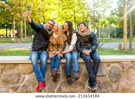 travel, vacation, people, technology and friendship concept - group of smiling friends making self portrait with smartphones in city park