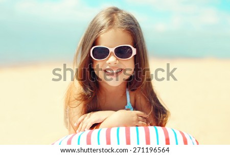 Travel, vacation - sunny portrait of smiling child resting on the beach in the summer day