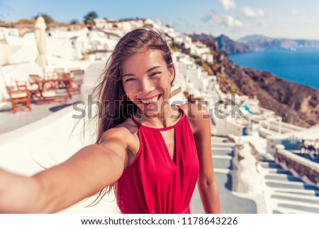 Travel vacation tourist girl selfie photo with phone on Santorini holiday. Happy asian woman in Oia smiling taking self-portrait picture with smartphone on summer vacation in Greece destination.
