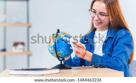 Travel vacations concept. Young smiling woman holds in hand airplane model. Happy beautiful girl planning vacation trip. #1484463236