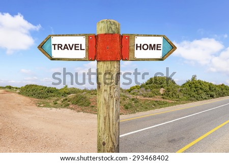 Travel versus Home messages - Wooden signpost with two opposite arrows on a road intersection with nature landscape in the background. Choice chance and change of lifestyle conceptual image