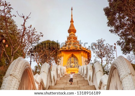 Travel with children to Thailand. Little boy climbs the stairs to the temple. Pattaya Wat Mondop Temple on the Hill
