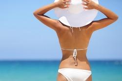Travel woman on beach enjoying blue sea and sky wearing white beach sun hat and bikini. Beautiful pretty stylish young asian model from behind on vacation holidays.