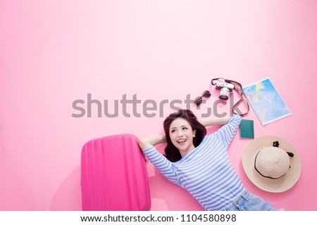 travel woman smile happily and look somewhere lying on pink floor