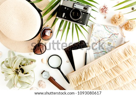 Traveler accessories on white background with retro camera, straw hat, bag, sunglasses, map and tropical palm leaf. Top view travel or vacation concept. Flat lay, top view. Summer background.