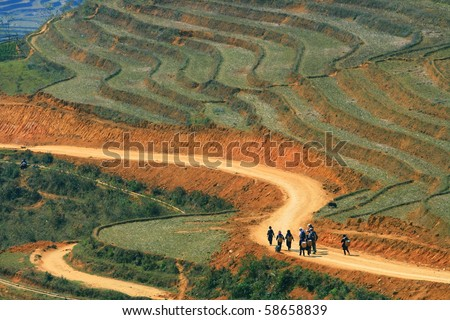 Traveler and hmong villager walk at Curve Dirt road in sapa with and paddle rice field