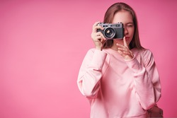 Traveler and photographer. Studio portrait of pretty young girl holding photocamera. Pink blackground.