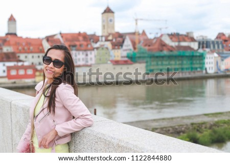 Traveler Asian lady with view city of Regensburg,Germany she wearing sunglasses and pink leather jacket smiling at camera enjoying her vacation in Europe