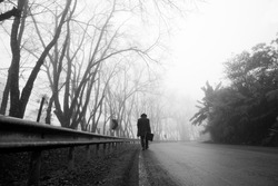Traveler asian man with a long coat and a bag. foggy misty road