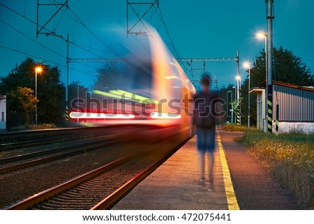 Traveler at the train station at the night. Young man with backpack walking on the platform. - blurred motion #472075441