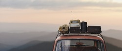 traveler car with roof rack and things in retro style on mountains background