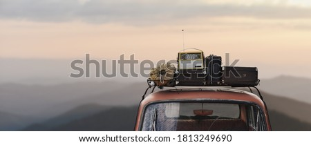 traveler car with roof rack and things in retro style on mountains background Foto stock ©