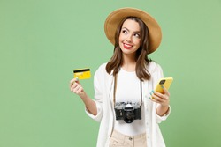 Traveler dreamful tourist woman in casual clothes hat camera hold mobile cell phone credit bank card isolated on green background Passenger travel abroad on weekends getaway Air flight journey concept