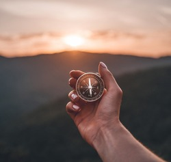 Traveler explorer young woman holding compass in a hand in summer mountains at sunrise, point of view.