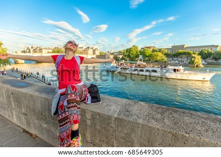 Traveler freedom concept. Caucasian lifestyle woman with open arms enjoying the Seine. Bateau-mouche and Pont Neuf on a blurred background. Tourist traveler and popular landmarks of Paris, France. Stock fotó ©