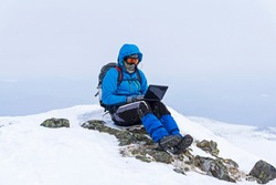 traveler freelancer works with a laptop in the winter in the wild mountains away from civilization