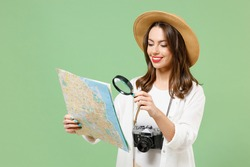 Traveler fun exploring tourist woman in casual clothes hat hold paper map look through magnifier loupe isolated on green background Passenger travel abroad weekends getaway Air flight journey concept.