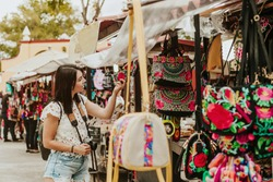 traveler girl buying souvenirs in the traditional Mexican market in Mexico streets, hispanic tourists standing in outdoor
