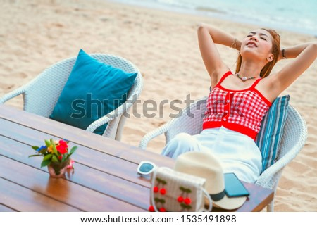 traveler girl in red dress sit on the chair in beach with vacation trip in emotional relax and smile for relax concept