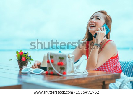 traveler girl in red dress sit on the chair in beach with vacation trip in emotional relax and smile for relax concept by happy in the use mobile phone
