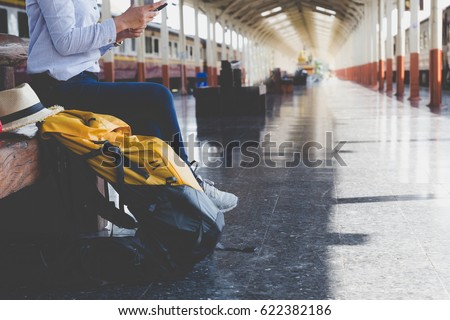 Traveler girl with a backpack sitting and waiting for train on the station. Outdoor adventure travel by train concept - Shutterstock ID 622382186