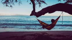 Traveler guy is relaxing in a hammock hang on tree directly on the beach. Man take a chilling moment during adventure vacation and enjoy the beauty of the Nature. Wanderlust and travel concept.