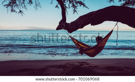 Traveler guy is relaxing in a hammock hang on tree directly on the beach. Man take a chilling moment during adventure vacation and enjoy the beauty of the Nature. Wanderlust and travel concept. #701069068