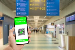 Traveler hand hold phone with health passport of vaccination certification. Health pass on phone at airport have been vaccinated of coronavirus covid-19. Safe travel concept, new normal for travelers
