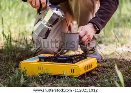 Traveler hands holding coffeepot and pouring coffee in cup near camping stove. Tourist man cooking with coffee maker and drinking from mug on picnic. Hiker with travel pot outdoors on nature. - Shutterstock ID 1120251812