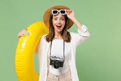 Traveler happy amazed tourist woman in casual clothes hat took off sunglasses hold inflatable swim ring isolated on green background Passenger travel abroad weekend getaway Air flight journey concept