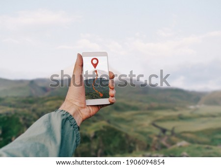 Traveler hiker man holding smartphone in a hand and using GPS app with trekking in summer mountains outdoor. Point of view in first person.