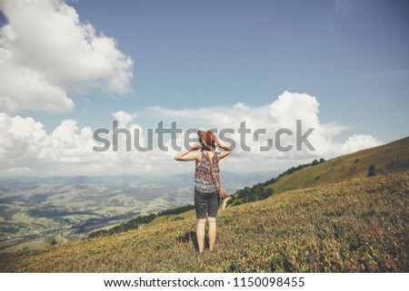 traveler hipster girl in hat, walking in sunny mountains, looking at clouds in sky. summer vacation. space for text. happy atmospheric moment. stylish woman traveling