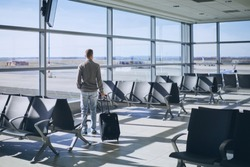 Traveler in airport terminal. Young man with luggage waiting for airplane.