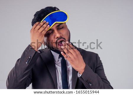 traveler indian business male wearing stylish classic suit and sleeping mask at studio white background