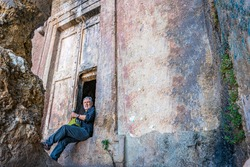 Traveler is drinking cold coffee at the rock tombs of Amyntas, also known as the Fethiye Tomb, is an ancient Greek rock-hewn tomb at ancient Telmessos, in Lycia, in Fethiye