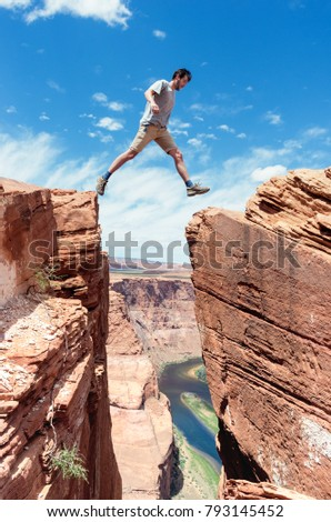 traveler jumps over rock at Horseshoe Bend in Utah, USA