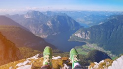 traveler legs in stylish green sneakers sitting on high alp mountain cliff enjoying scenery mountain top. Pov view Hiking freedom concept Austria Hallstatter See lake Krippenstein mountain Hallstatt