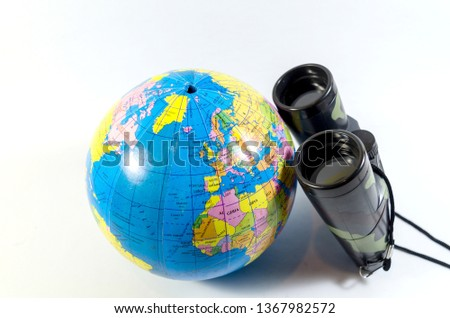 Traveler locating place by a binocular for a travel destination symbolize globe as a world isolated in white background #1367982572