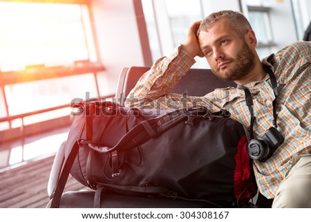 Traveler looking into far.\ Portrait of bearded man inside airport terminal pensive casual shirt and travel pants sitting next to his backpack luggage large bright window on background