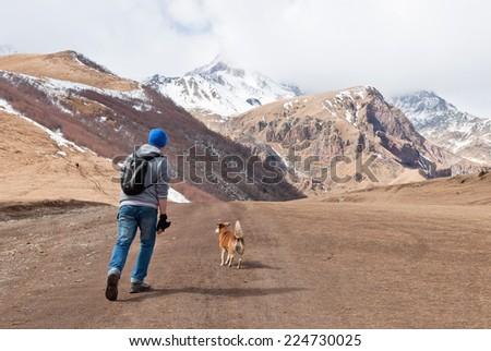 Traveler man and dog running on the road of  Kazbegi-Gergeti village, Georgia, Caucasus