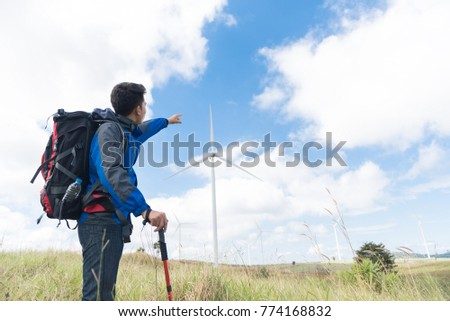 83efa6d8bd12 Traveler Man climbing look at the Wind turbines generating electricity with backpack  Travel Lifestyle concept active