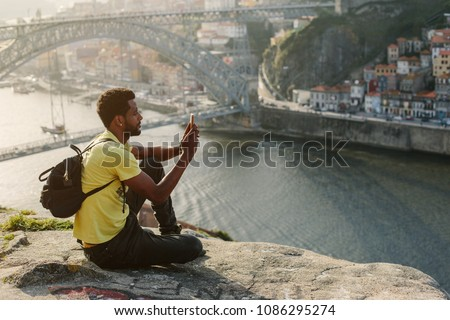 Traveler man doing photo on mobile phone. Porto, famous iron bridge and Douro rive on background  #1086295274