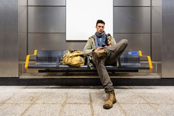 Traveler man is using mobile phone, while sitting at underground station and waiting the train. Young male making a brake on the bench with luggage, using wireless internet to connect to social media.