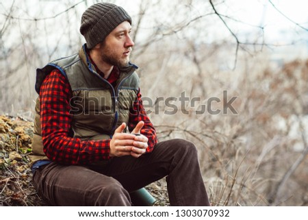312ab99bf3 Traveler man pouring from thermos and drinking hot tea or coffee during  adventure in park