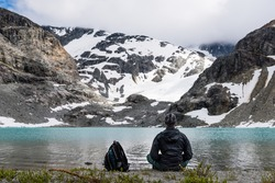 Traveler man sitting meditation lotus pose near the mountain lake and enjoying panoramic view of Wedgemount lake British Columbia Canada. Healthy lifestyle concept.
