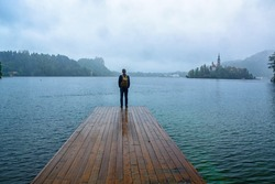 traveler man standing on the lake wooden pier in fog against island with church. travel lifestyle concept. Bled lake, Slovenia