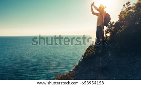 Traveler man stands on the top and takes pictures of sea on cell phone camera during sunset #653954158