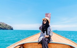 Traveler muslim woman sitting over thai boat on summer time. Travel and vacations Concept.
