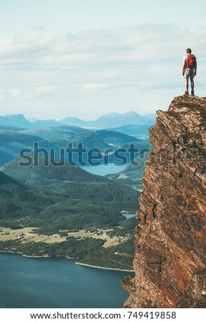 Traveler on cliff mountains over fjord enjoying Norway landscape Travel Lifestyle success motivation concept adventure active vacations outdoor #749419858