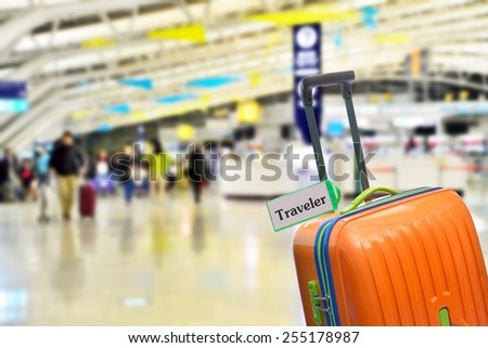 Traveler Orange suitcase with label at airport